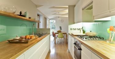 Стеклянный фартук изумрудно-зеленого цвета в интерьере кухни