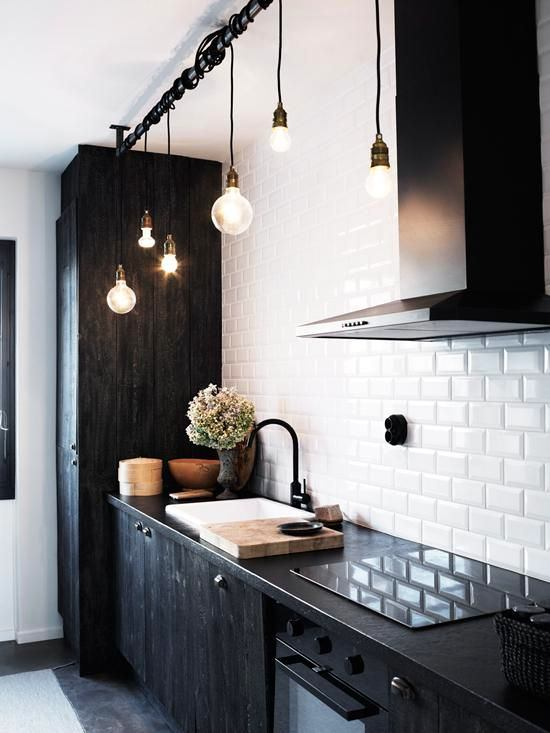 Черная кухня на фоне белой стены