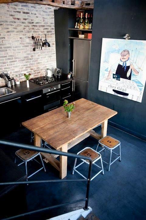 Деревянный стол в окружении черной кухни