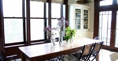 Обеденный стол из натурального дерева в оригинальном интерьере кухни-столовой