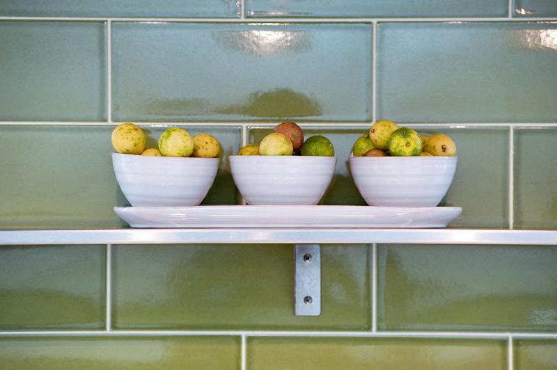 Белые миски с фруктами на открытой полке