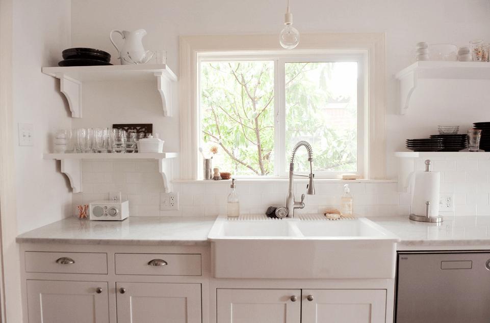 Окно над рабочей стойкой в белой кухне