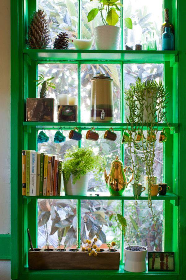 Оформление кухонного окна зелёными домашними растениями в керамических горшках