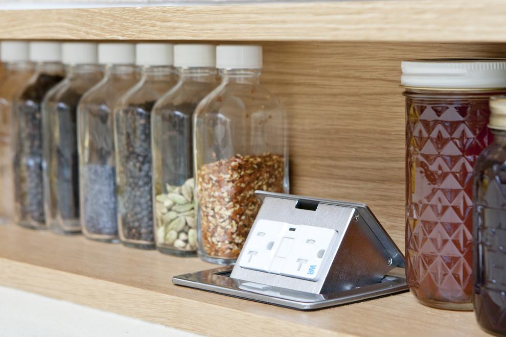 Стеклянные контейнеры для хранения специй на открытой полке в интерьере кухни