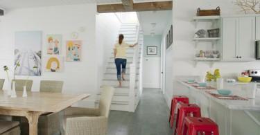 Стильные табуреты Tolix красного цвета в светлом интерьере кухни от Rethink Design Studio