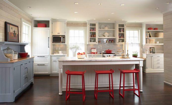 Потрясающий дизайн интерьера белой кухни с красными барными стульями