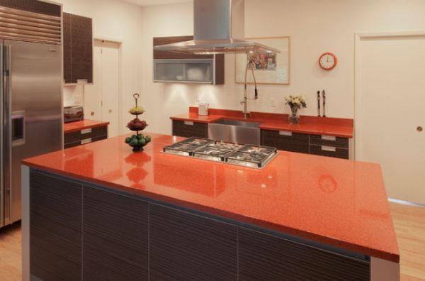 Стеклянная столешница терракотового цвета в оформлении кухонного острова из натурального тёмного дерева