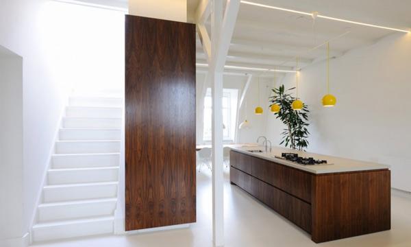 Деревянный кухонный гарнитур со светлой столешницей в интерьере