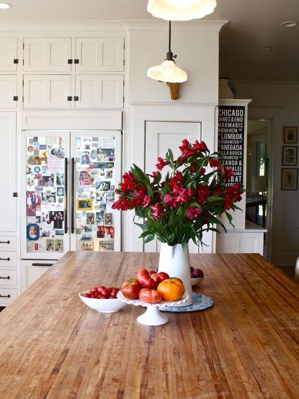 Керамическая ваза с красными цветами на деревянном кухонном столе