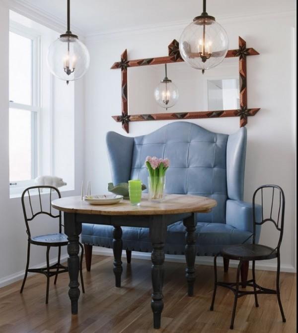 Большой мягкий диван у обеденного стола в интерьере кухни