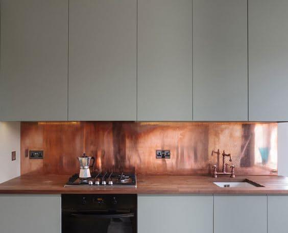 Дизайн кухни с медью: оригинальный фартук над плитой