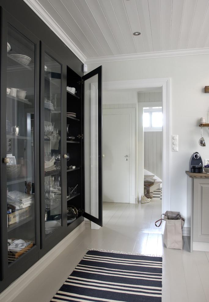 Чёрный буфет с прозрачными дверцами в интерьере белой кухни