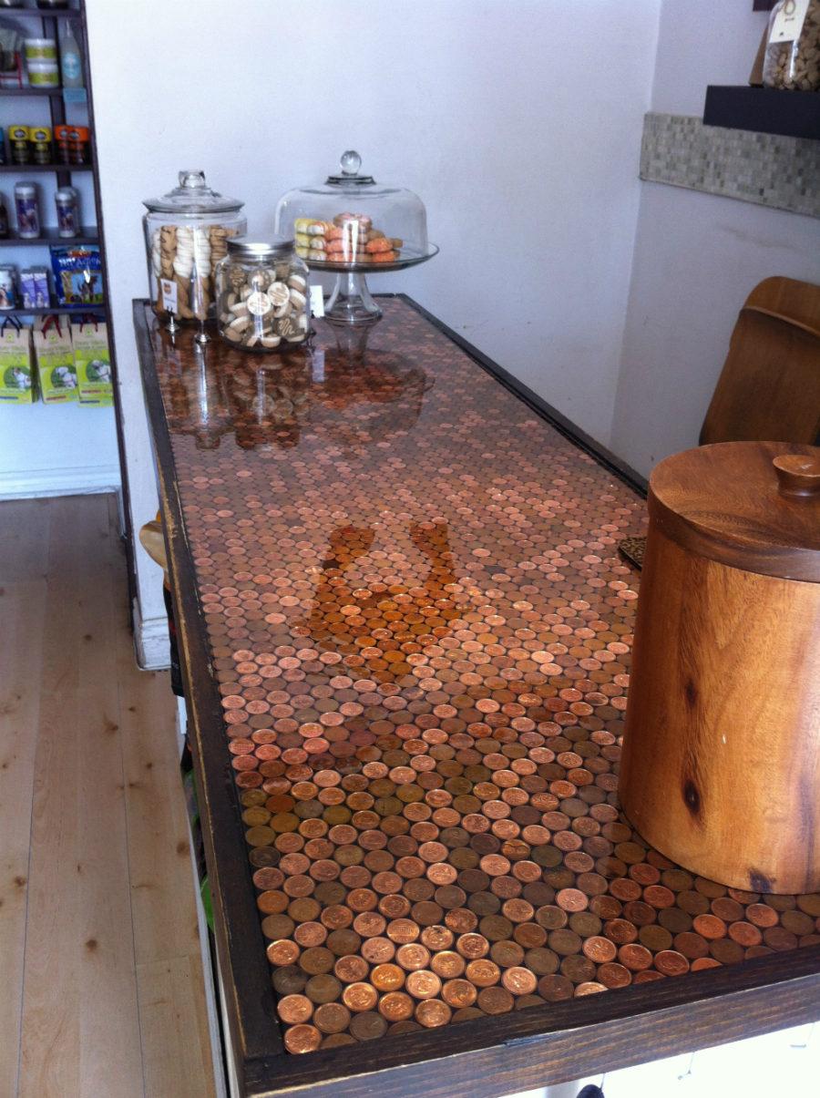 Элегантный дизайн кухонной столешницы для острова - разложенные под стеклом старинные монеты