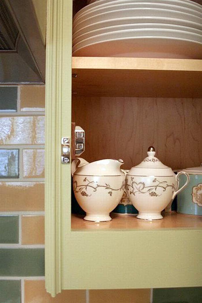 Красивые расписные чайнички на полках кухонного шкафчика