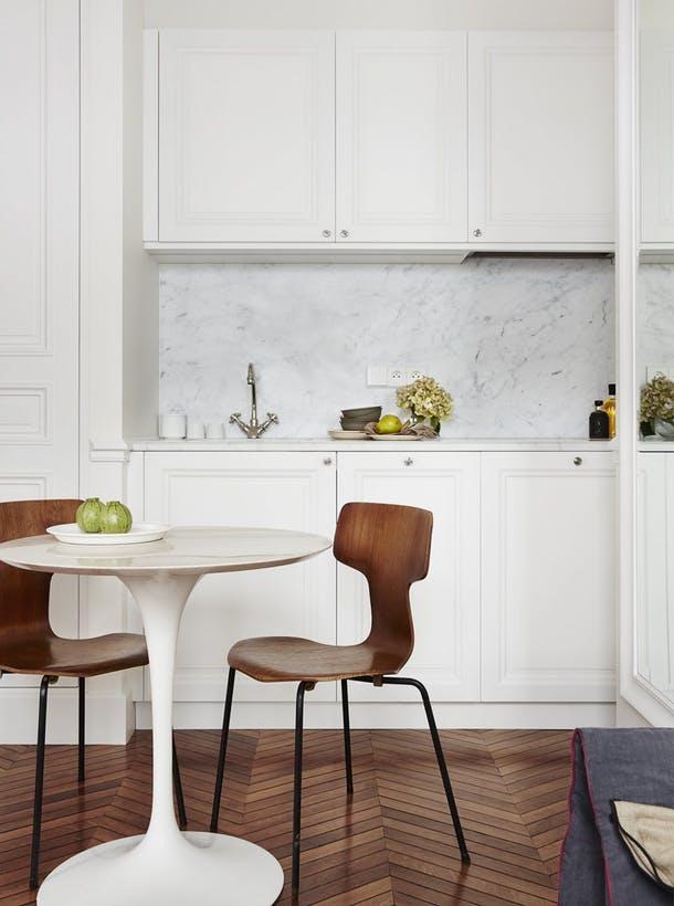 За белоснежными панелями шкафов спрятаны посудомоечная машина, вытяжка и холодильник