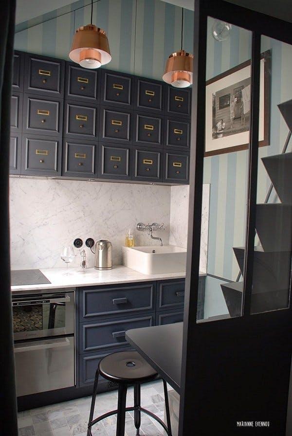 Тёмные цвета, мраморная столешница и дизайнерская мойка придают кухне шикарный вид