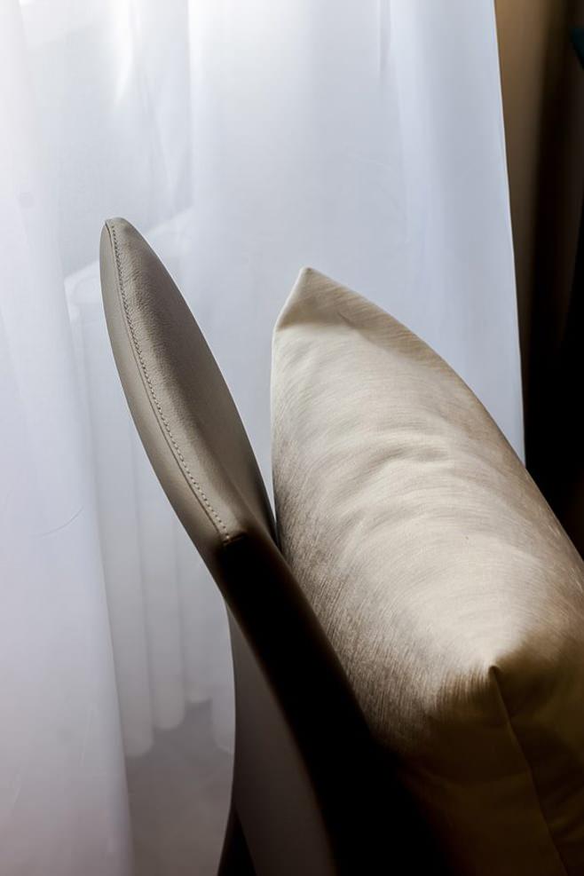 Декоративная подушка нейтрального оттенка на коричневом стуле