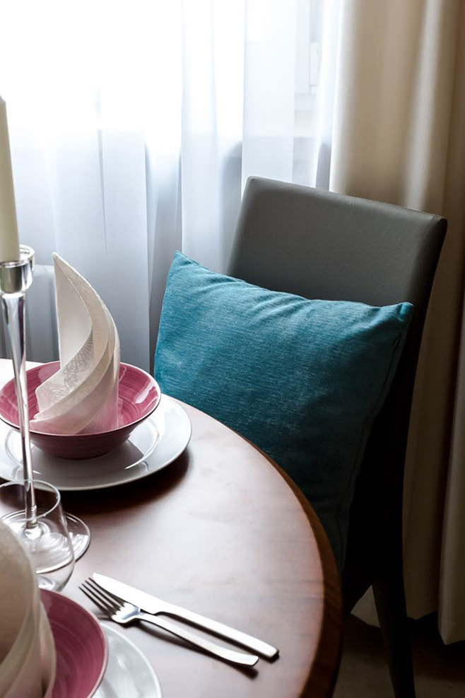 Декоративная подушка бирюзового цвета на коричневом стуле