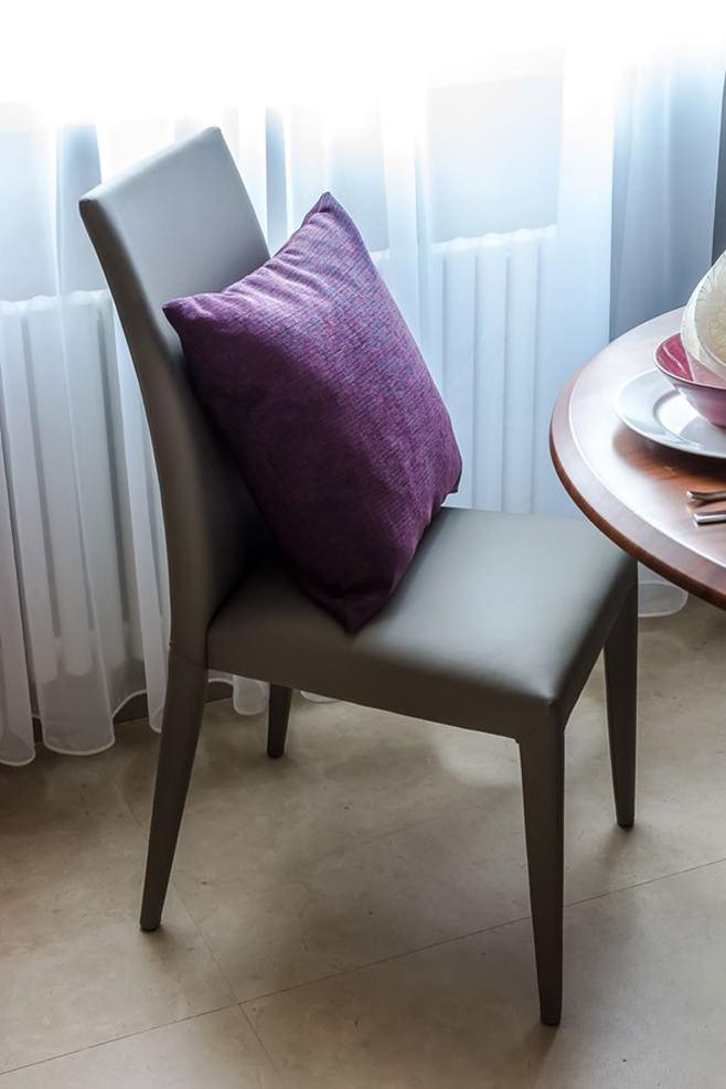 Фиолетовая декоративная подушка на сером стуле в интерьере кухни-столовой