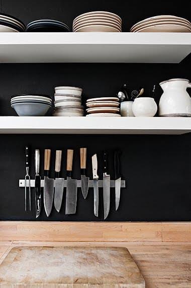 Интерьер чёрно-белой кухни: белые полки на фоне тёмной стены