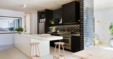Интерьер просторной кухни с тёмной кирпичной стеной