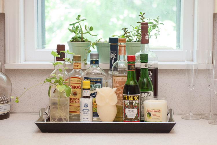 Бутылки с вином, маслом, уксусом и приправами на подносе