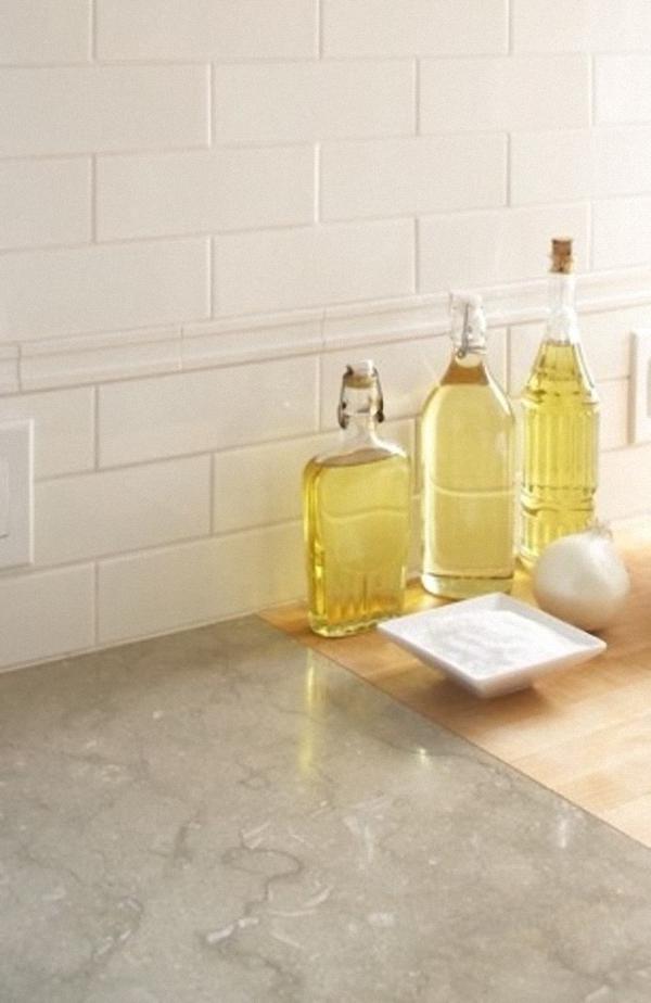 Бутылочки разной формы для хранения масла на мраморной столешнице кухни