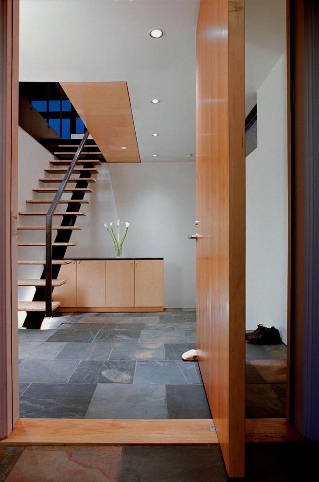 Почернённая стальная лестница с деревянными ступенями, ведущая на второй этаж дома