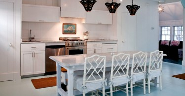 Чёрные абажуры подвесных светильников в интерьере белой кухни