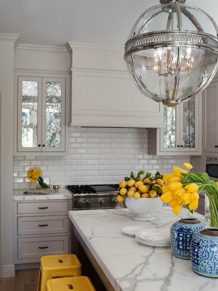 Белые кухонные шкафы с серыми столешницами на кухне