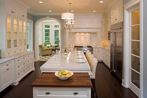 Изящная белоснежная кухня с мраморными столешницами и шкафами со стеклянными дверцами