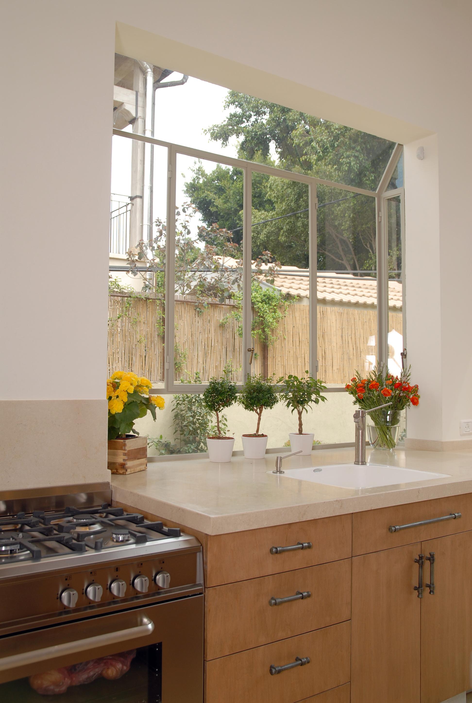 Домашние цветы на подоконнике за кухонной мойкой