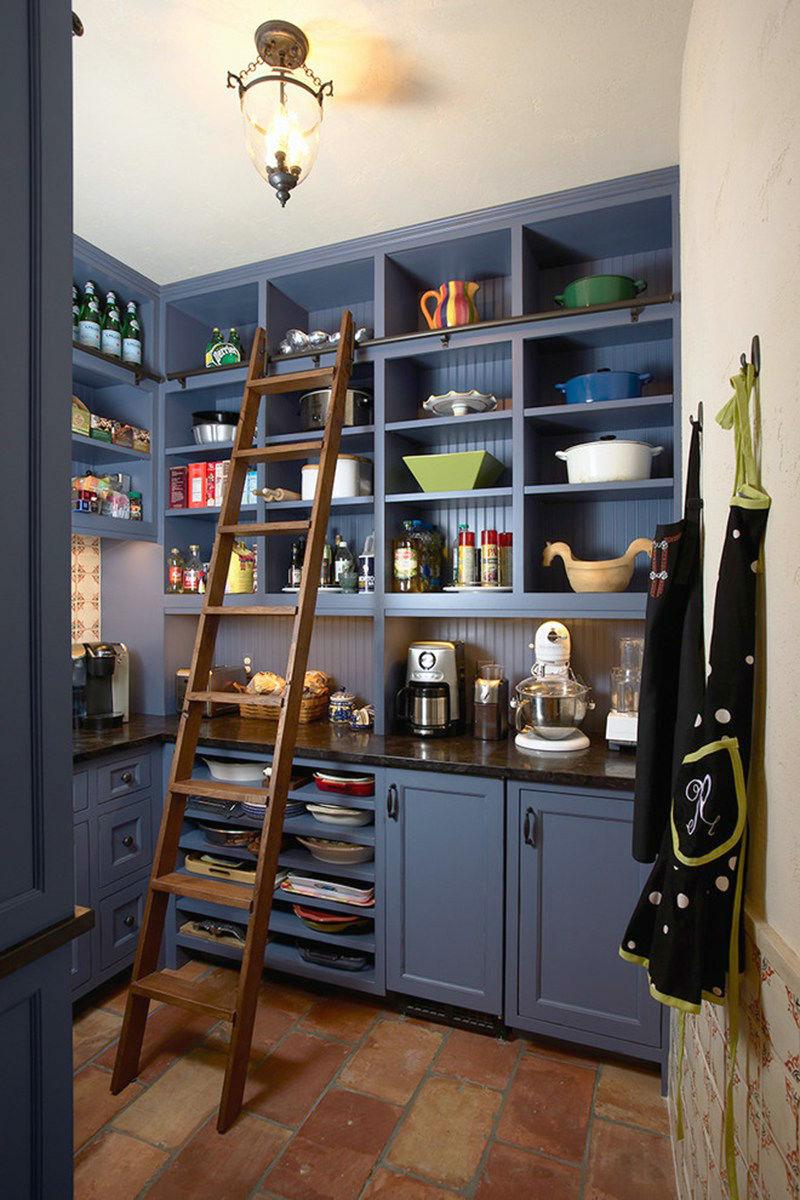Деревянная лестница к высоким полкам кухонного шкафа в синей гамме