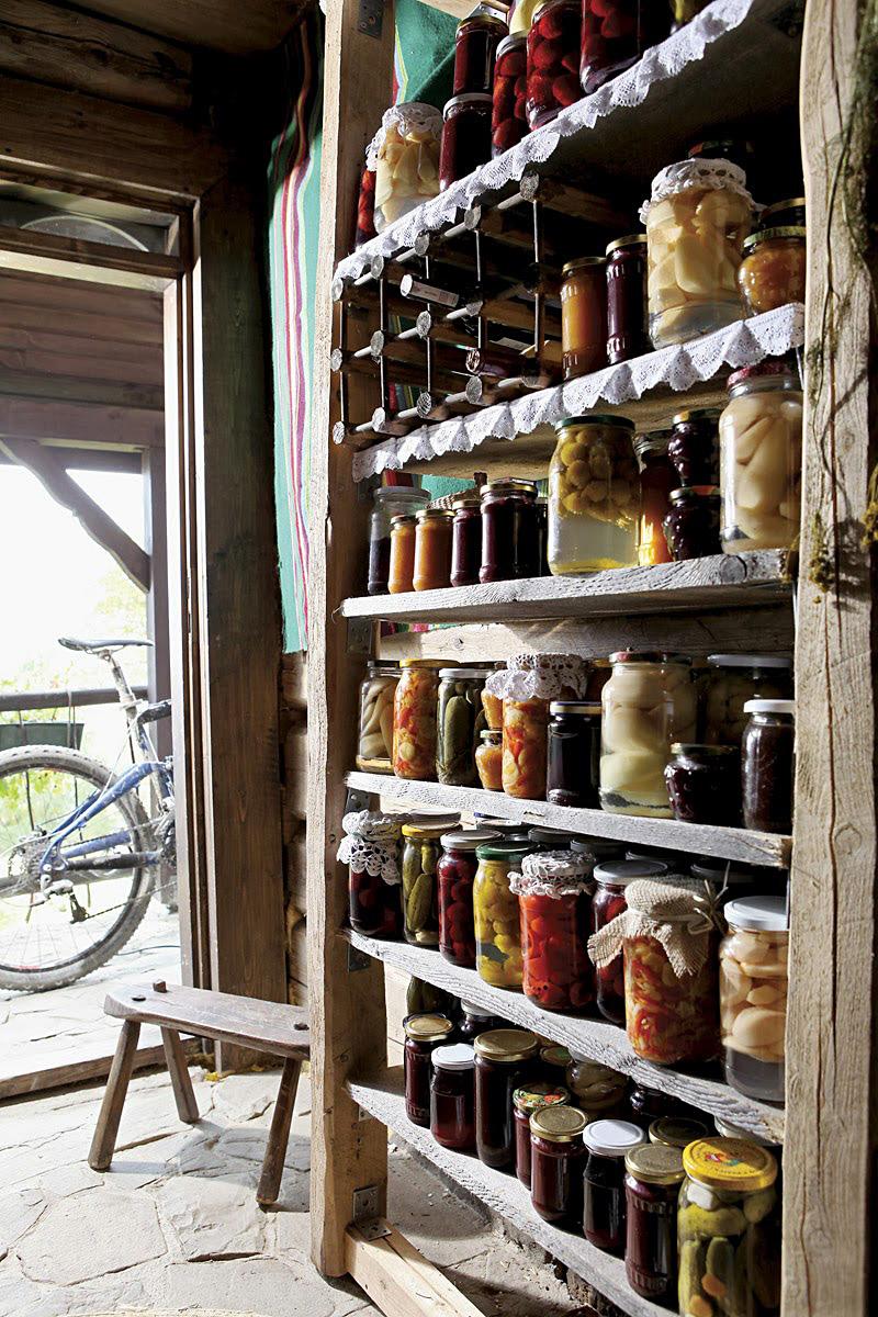 Открытые деревянные полки с банками домашних заготовок: варенья и джема