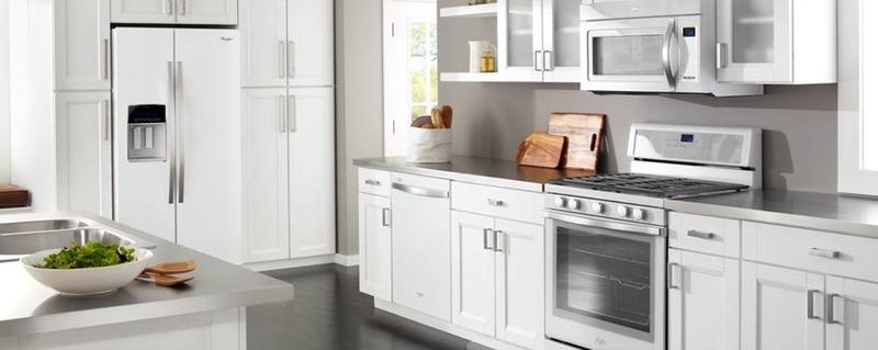 Кухня с белой мебелью и металлической техникой