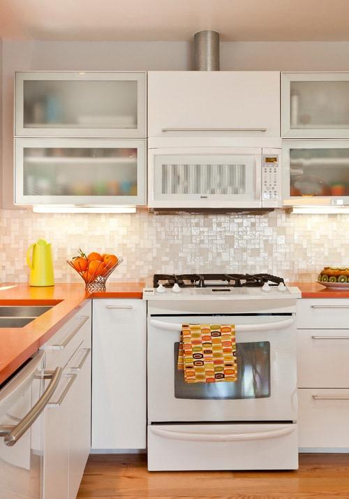 Белая кухня с оранжевыми поверхностями