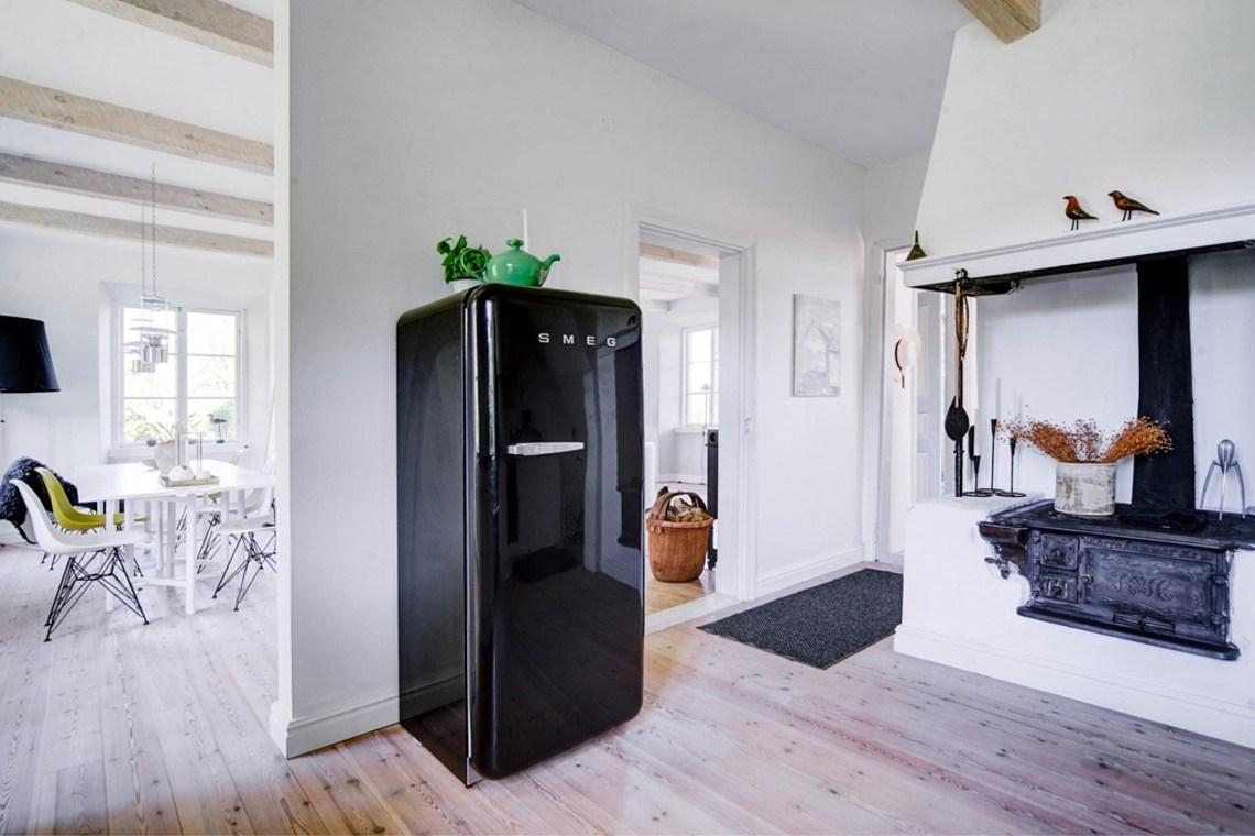 Отдельно стоящий черный холодильник в интерьере