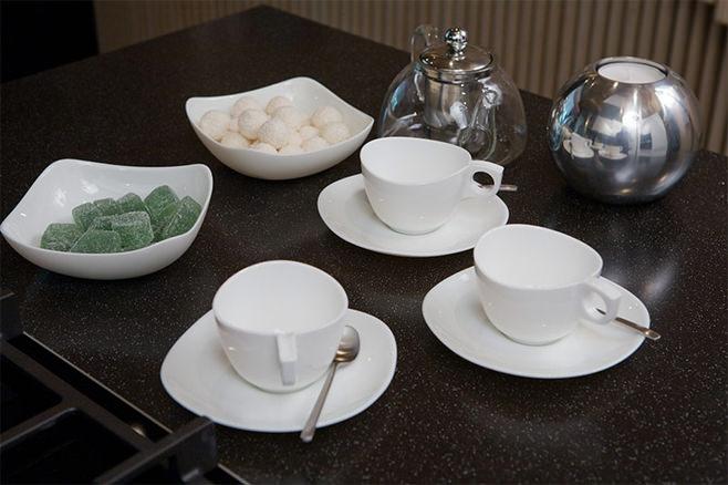 Сервировка стола к чаепитию белой керамической посудой