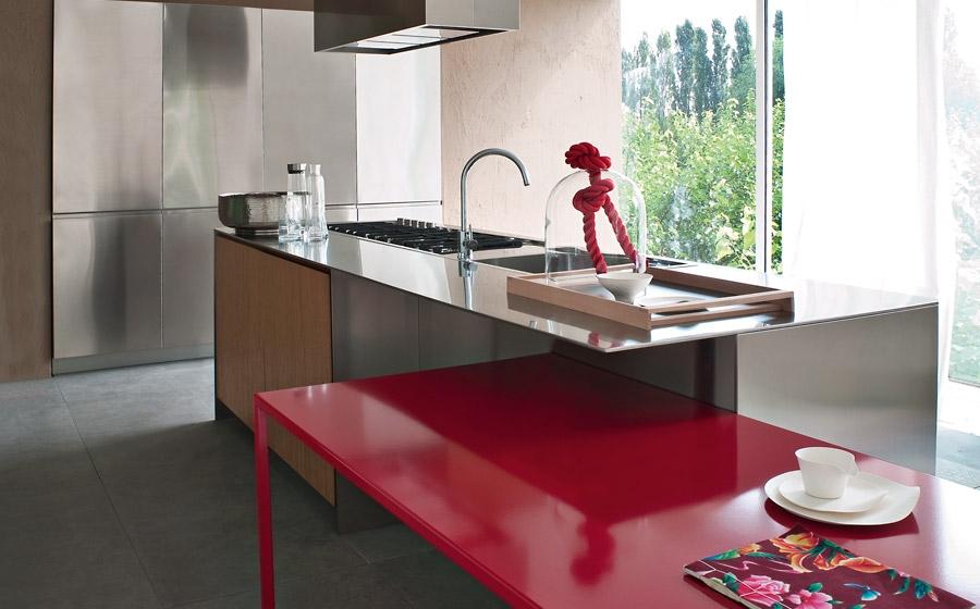 Кухонный остров из нержавеющей стали на фоне глянцевого красного стола