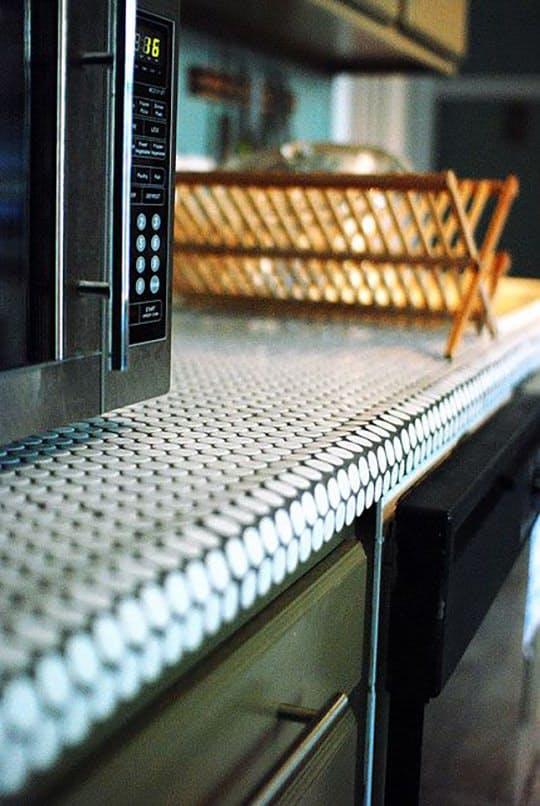 Облицовка столешницы плиткой: светло-голубые кружочки плитки-пенни очаровательно огибают край стола
