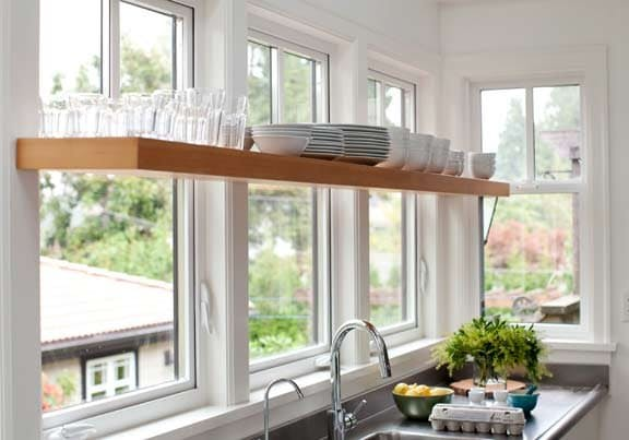 Необычный, но интересный вид создают открытые полки на кухне перед окнами