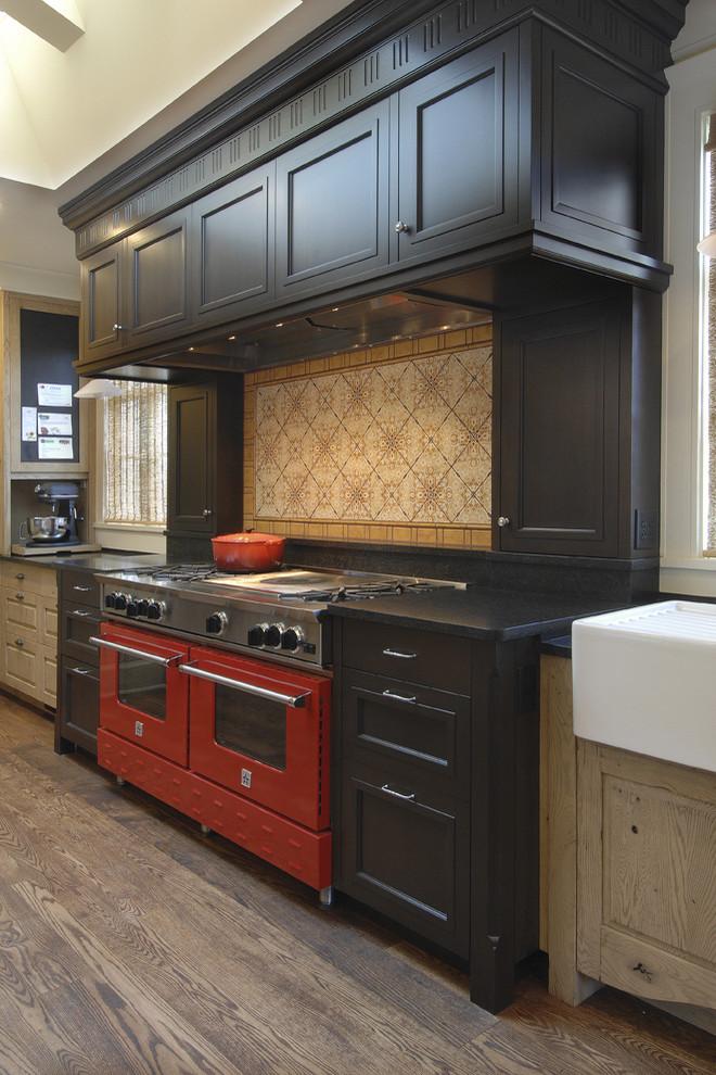 Ярко-красная встроенная плита в интерьере кухни  из тёмного дерева