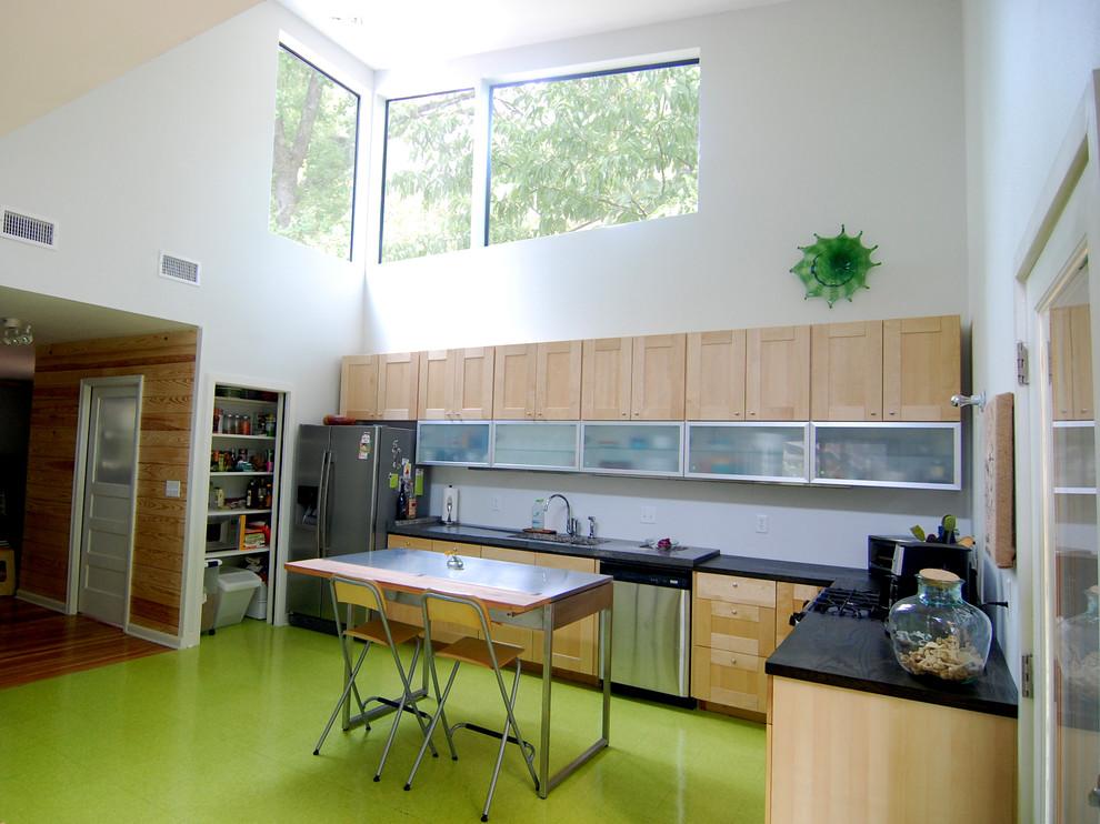 Кухонный гарнитур светлого дерева  на фоне ярко-зелёного напольного покрытия
