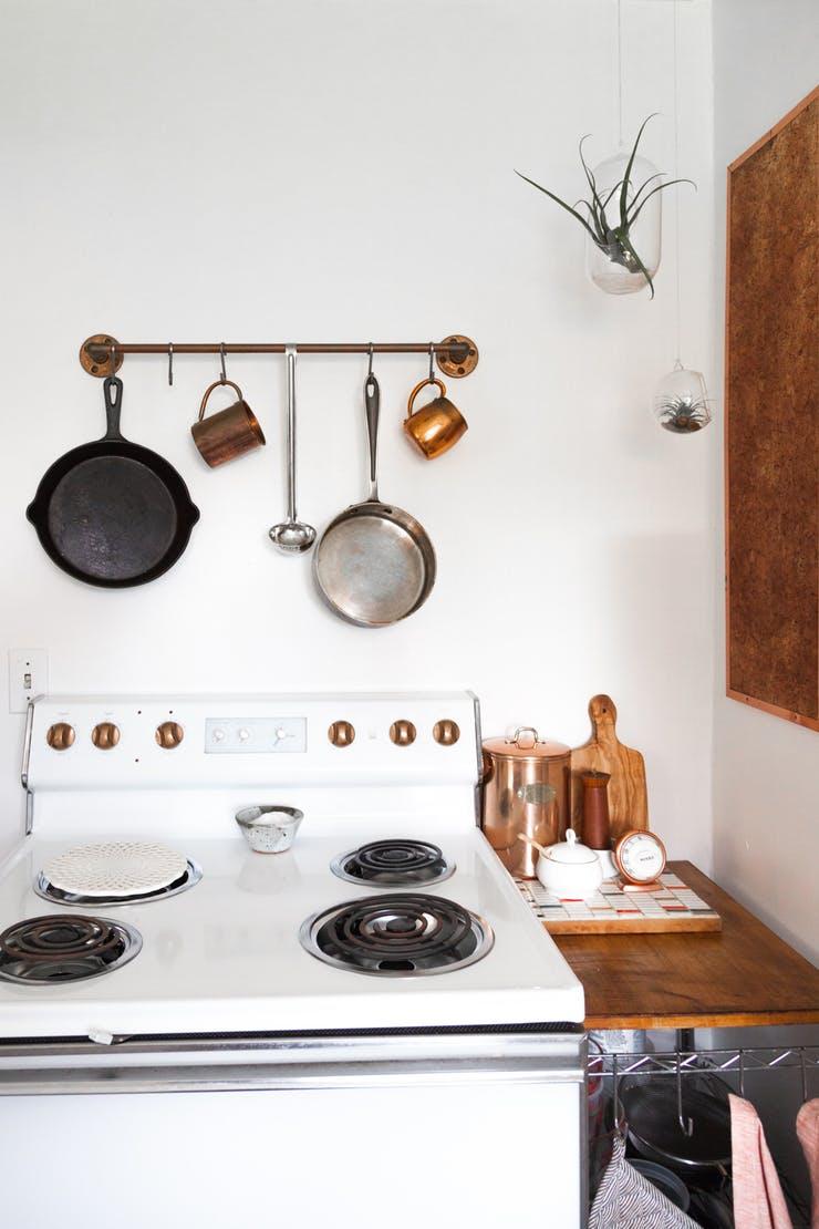 Подвесная кухонная утварь над кухонной плитой