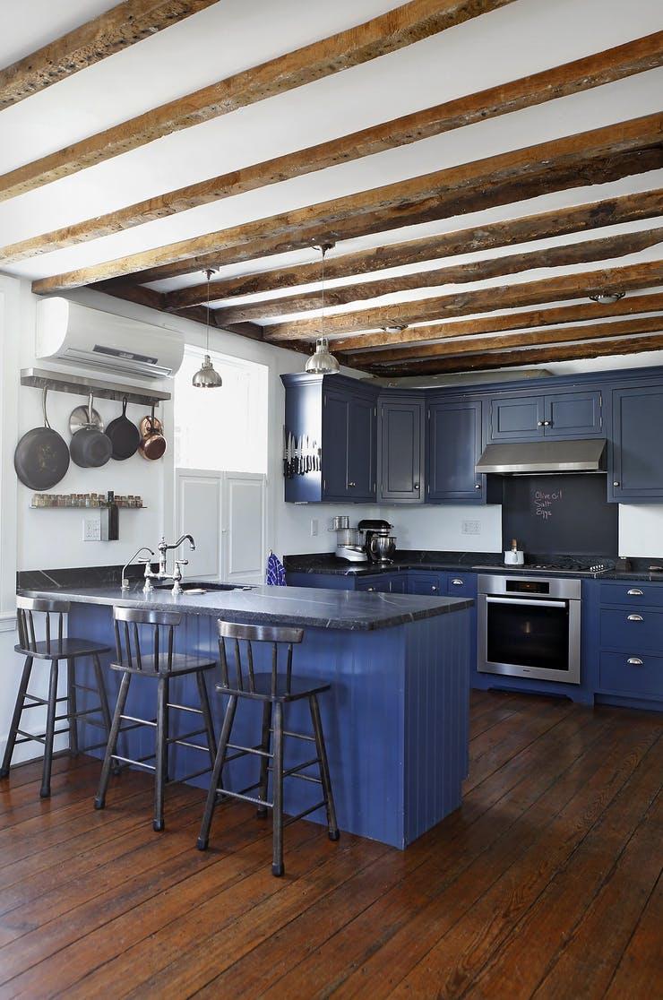 Подвесная кухонная утварь в интерьере синей кухни