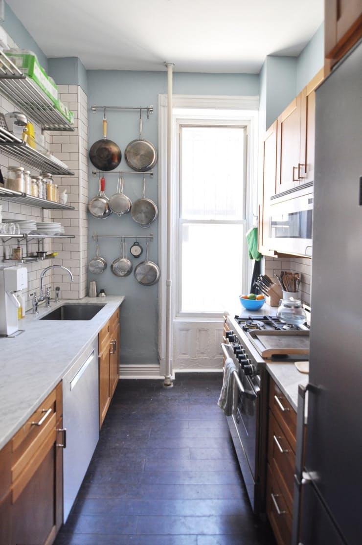 Подвесная кухонная утварь в интерьере узкой кухни