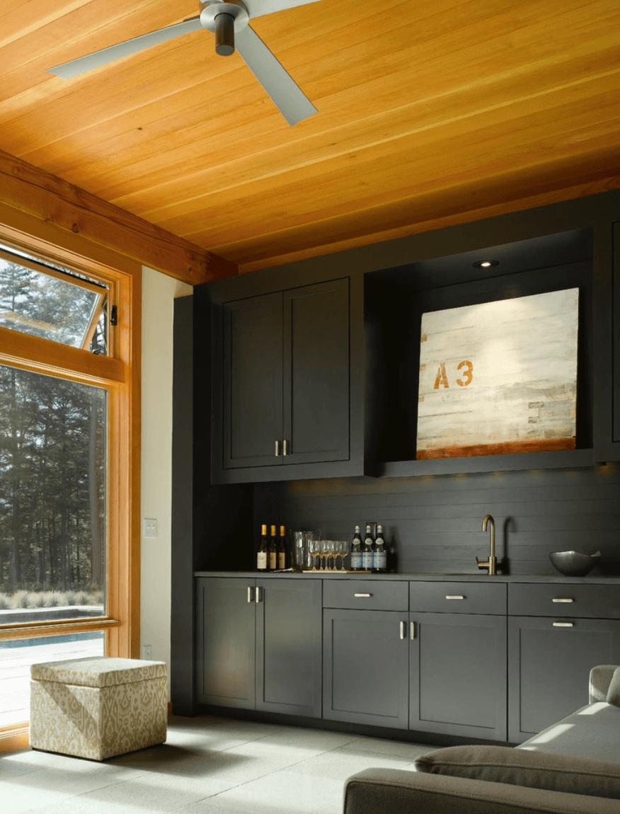 Кухня исполнена в черным цвете с фартуком из дерева