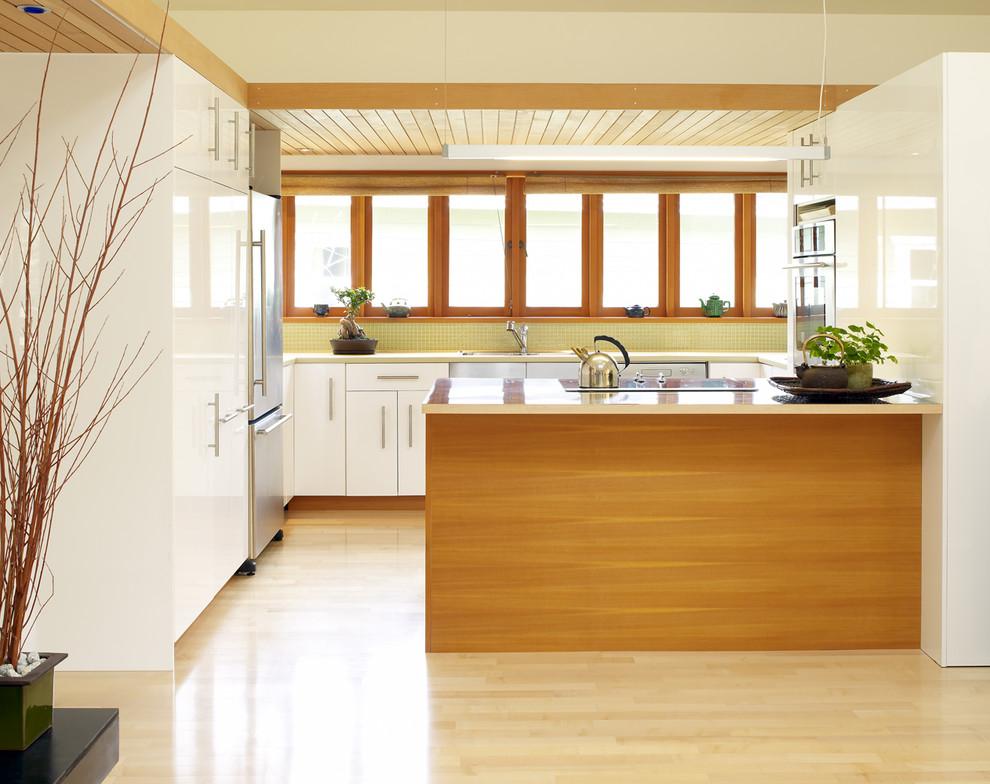 Оригинальный дизайн интерьера белой кухни с деревянными акцентами от Works Photography Inc.