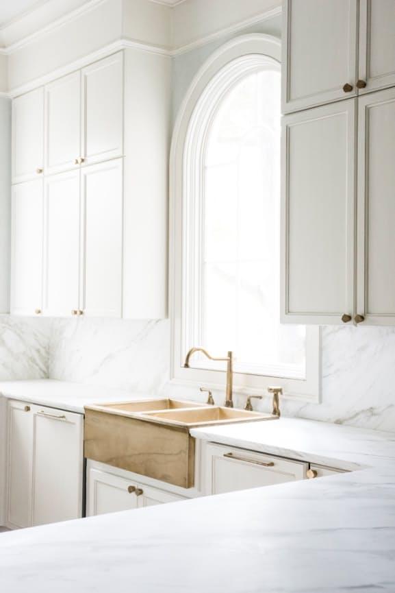 Шикарная белая кухня: раковина перед арочным окном