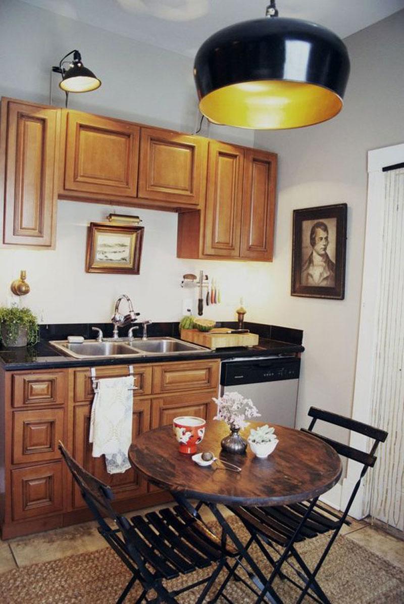 Винтажный круглый столик из натурального дерева в интерьере маленькой  кухни